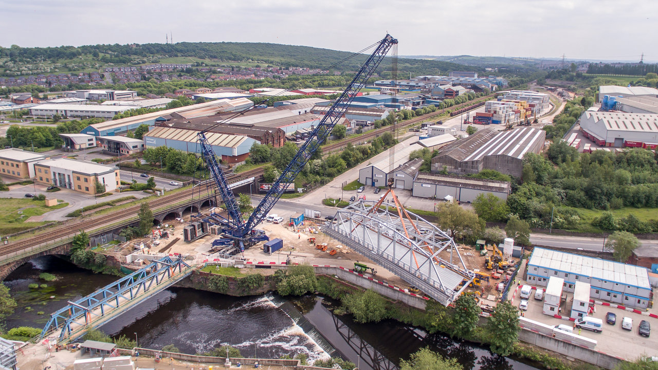Reidsteel prefabricated steel through truss bridge is swung into place with the help of an 850T mobile crane